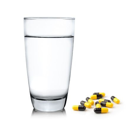 Glass of water and pills isolated on white background photo