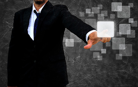 businessman hand pushing button on a touch screen interface in the old texture Stock Photo