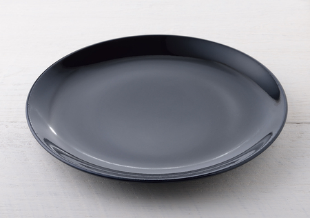 ceremic: Empty black plate on wooden table