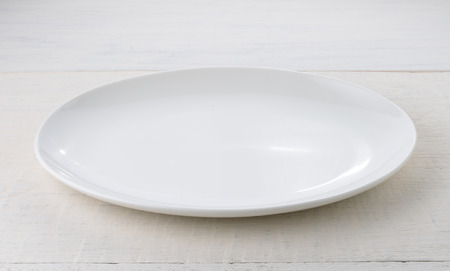 Empty ceramic plate on wooden table