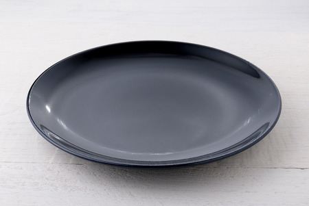Empty black ceramic plate on wooden table Banque d'images
