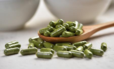 Moringa capsule pills in the woodspoon