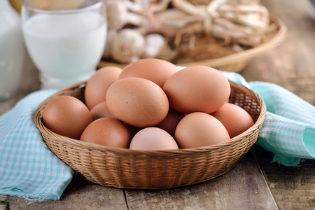 eggs in a basket on wooden table photo
