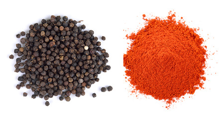 Pile of red paprika powder and Black pepper seeds on white background