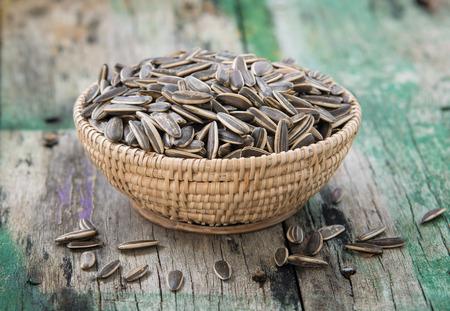 semillas de girasol: semilla de girasol en la cesta sobre la mesa de madera Foto de archivo