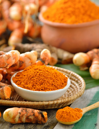 curcumin: turmeric roots in the basket on wooden table