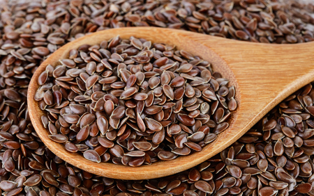 Flax seeds heap in wood spoon Imagens