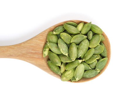 pumpkin seeds in the spoon on white background