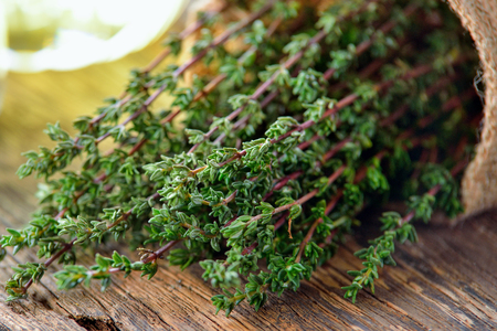 Thyme herb in basket on wooden table.