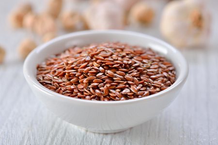 Flax seeds in bowl on table
