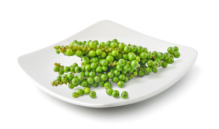 Bunches of fresh green peppercorn in a plate isolated on white background