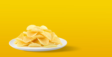 Potato chips in a plate on yellow background. with Copy space for your text. Stock Photo