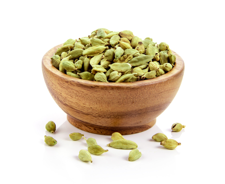 cardamom in wood bowl isolated on white background