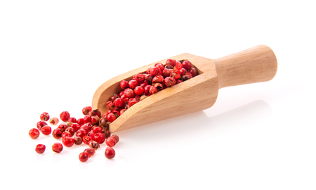 pink peppercorn  in wood scoop isolated on white background