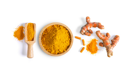 Turmeric (Curcuma) powder pile in wood bowl  and capsule isolated on white background