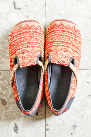 Handmade cloth shoes on marble photo