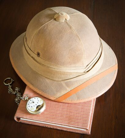 pith: Old pith helmet and pocket watch on the book