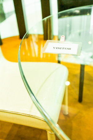 White visitor plastic card on glass table