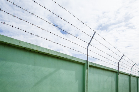 prison system: barbed wire wall against the sky, Backgrounds Stock Photo