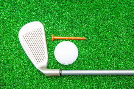 silver: Golf ball, iron and tee on artificial green grass detail macro Stock Photo
