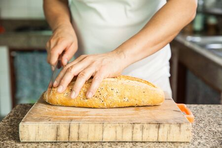 Slicing a whole grain bread with a knife