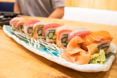 Salmon & tuna sushi roll on ceramic plate on wooden table in Japanese restaurant