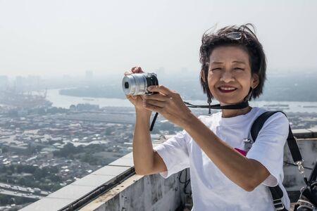 A girl take a photo at rooftop of Maleenont tower at Rama 4 road Bangkok Thailand, December 9, 2019