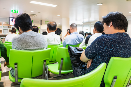 People sitting on chairs waiting in queue to wait for treatment from doctors in the Kluaynamthai Hospital at Rama 4 road Bangkok Thailand,  March 13, 2019