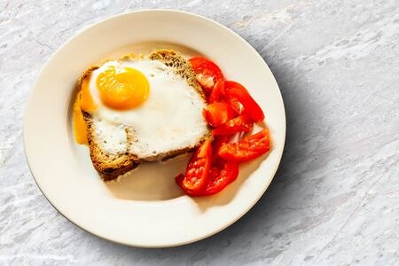 Cooked eggs by baking and whole wheat bread on a white plate Banco de Imagens