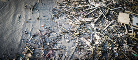Old rubbish pollution stuffs on the bank of river in Bangkok
