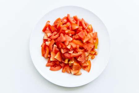 Sliced tomato on white plates on white background