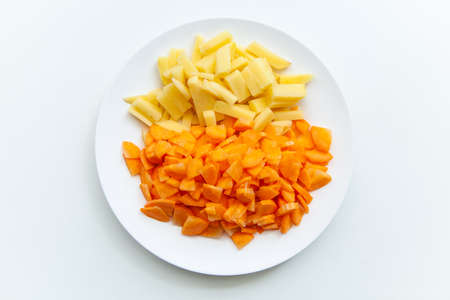 Sliced carrots and potatoes in white plate on white background