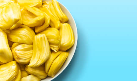 Jackfruit in a white bowl isolated on blue background