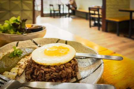 Fried eggs on brown rice and  baked chicken in plates with salad bowls on the table in Thai restaurants