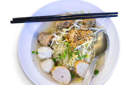 Yellow noodle in soup with meatball fish in a bowl, Thai food style