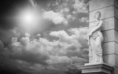 Woman statue with cloudy sky background