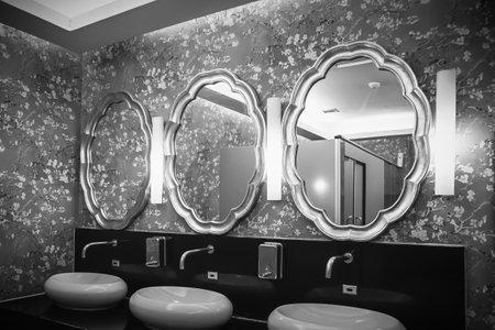 Retro style mirrors, washbasins and soap tank in public toilet room at Community Mall Sukhumvit road in Bangkok