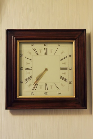 wooden clasical wall clock hanging on the wall photo