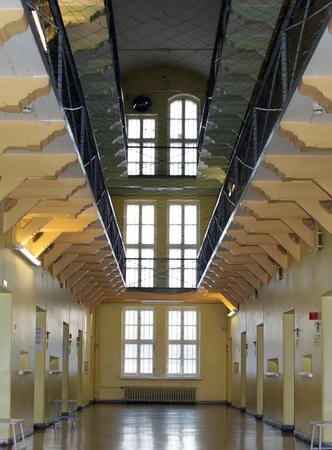 cellule prison: Regardant vers le bas d'une all�e d�serte bord�e des deux c�t�s avec trois niveaux de cellules de prison.