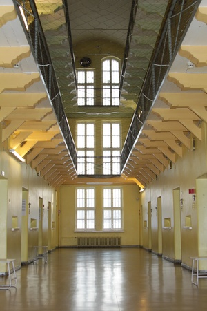 prison system: Looking down a deserted aisle lined on both sides with three levels of prison cells.