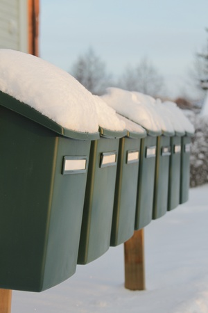 A row of green mailboxes draped with a layer of freshly fallen snow photo