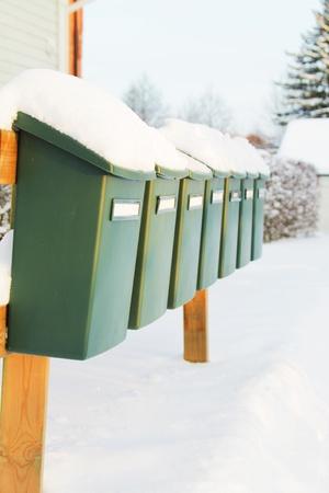 freshly fallen snow: Una fila di caselle di posta verde drappeggiato con uno strato di neve fresca