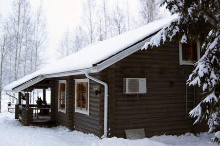 wooden cottage covered by snow