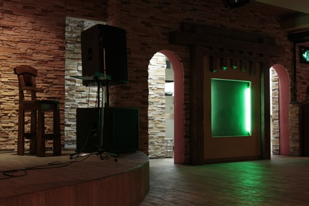 Stage with speaker in cafe with green illuminated niche