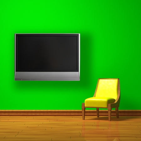Yellow chair with LCD tv on the wall in green minimalist interior photo