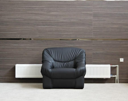 Alone black chair with radiator in minimalist interior photo
