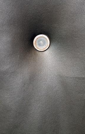 Dark grungy door leather with peeling door spy hole Stock Photo
