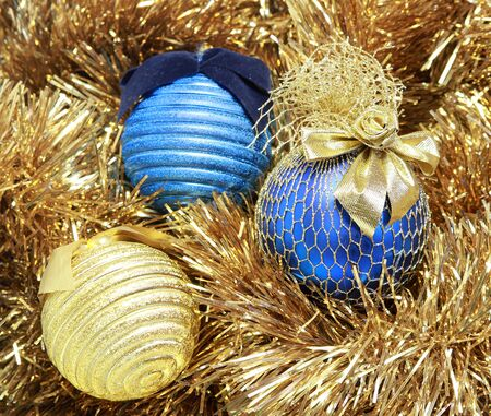 blue and golden christmas balls on a golden tinsel photo