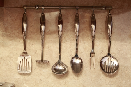 set of kitchen utensils hanging on the wall  photo
