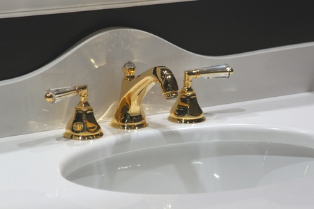 White and clean washbasin and golden tap  photo